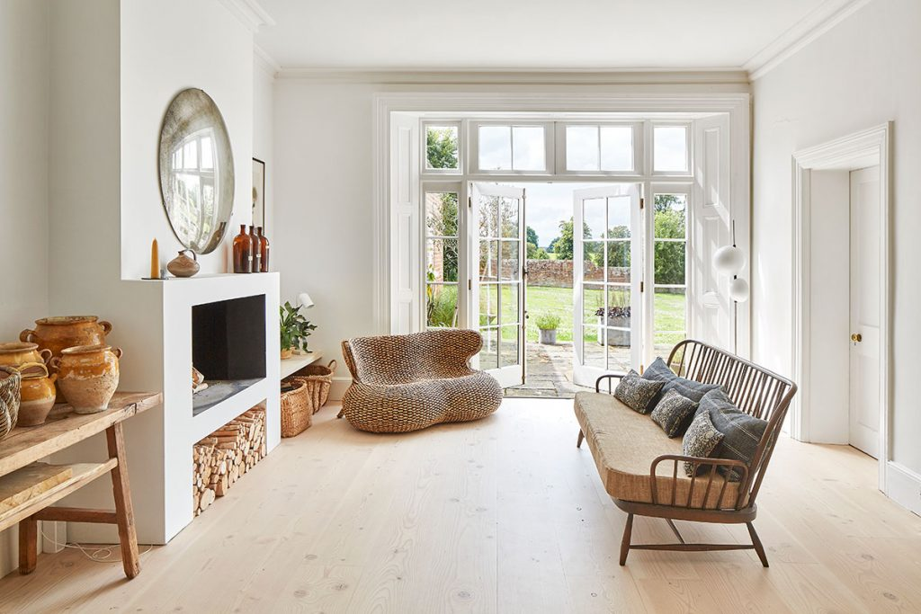 Vintage Ercol sofa, vintage confit pots and wicker sofa and french doors at the home of Simone-Bunting in Pangbourne, Berkshire. Credit: The-Modern-House