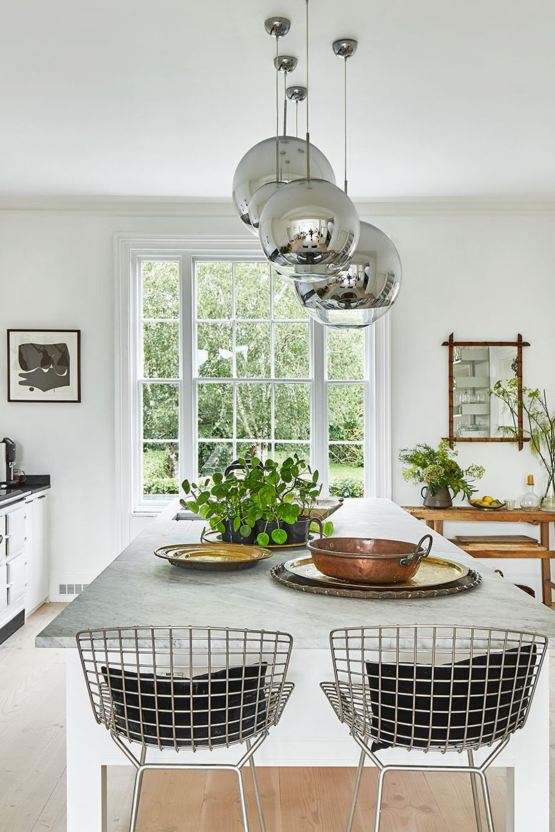 White walls, white range cooker, kitchen island and open shelving in the kitchen at the home of Simone-Bunting in Pangbourne, Berkshire. Credit: The-Modern-House