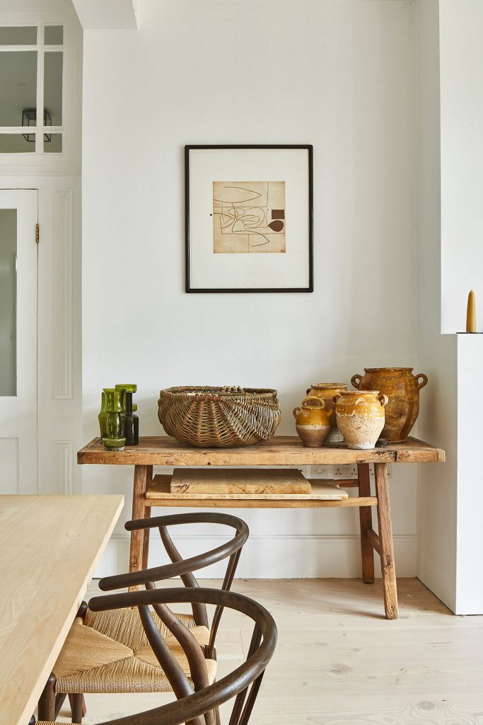 Vintage wooden side table, green glass vases, contemporary art and vintage confit pots in the kitchen at the home of Simone-Bunting in Pangbourne, Berkshire. Credit: The-Modern-House
