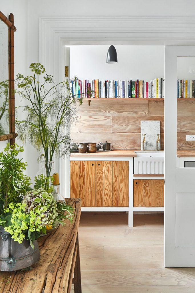 Wooden fronted units, wooden backsplash and open shelf in the utility room at the home of Simone-Bunting in Pangbourne, Berkshire. Credit: The-Modern-House