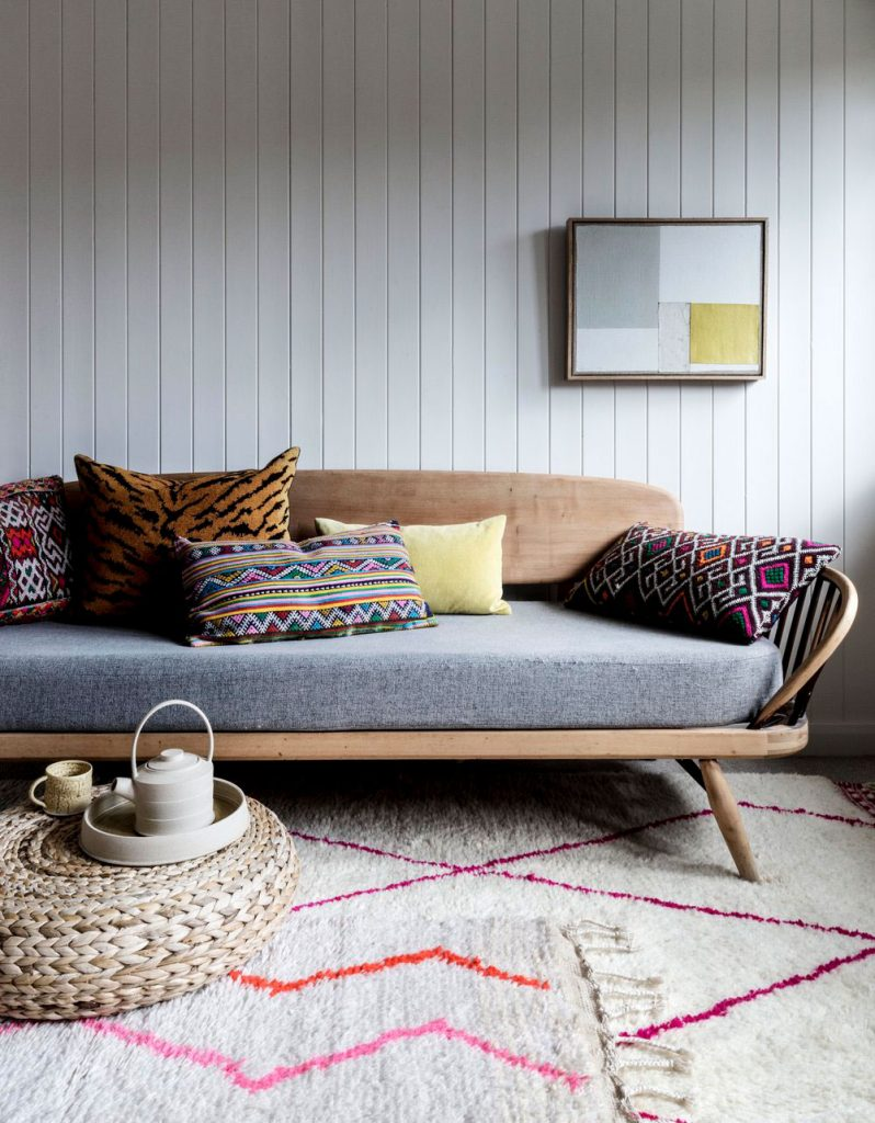 Mid century wooden sofa, shiplap walls, abstract art and selection of rugs from Tate & Darby