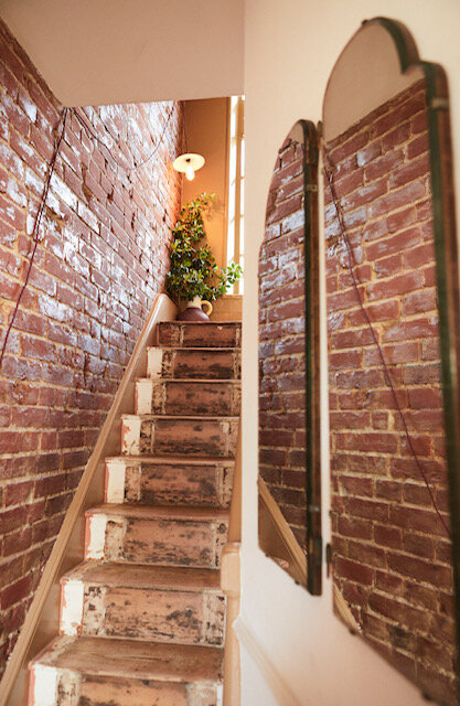 Sophie Rowell interior designer Côte. de Folk stairwell exposed brick and antique mirrors