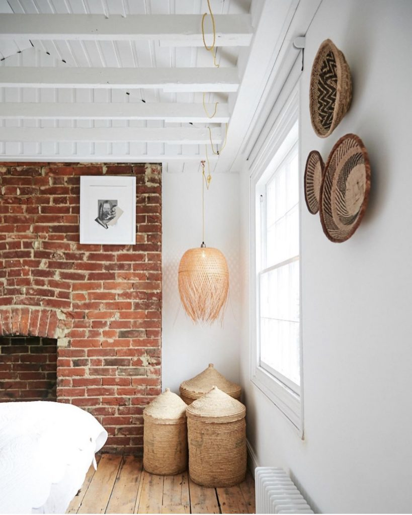Sophie Rowell interior designer Côte de Folk bedroom with baskets on the wall, exposed rafters and brickwork