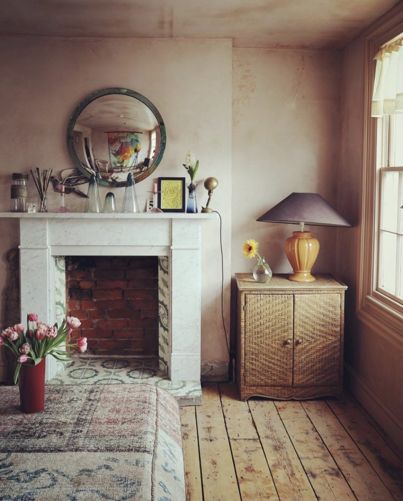 Sophie Rowell interior designer Côte de Folk sitting room with plaster walls, a vintage convex mirror and rattan cupboard