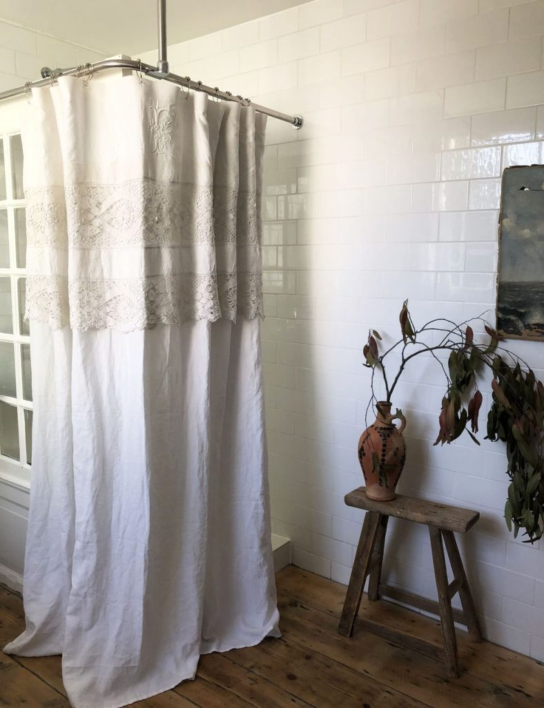 Sophie Rowell interior designer Côte de Folk bathroom antique door shower screen and vintage linen and lace shower curtain