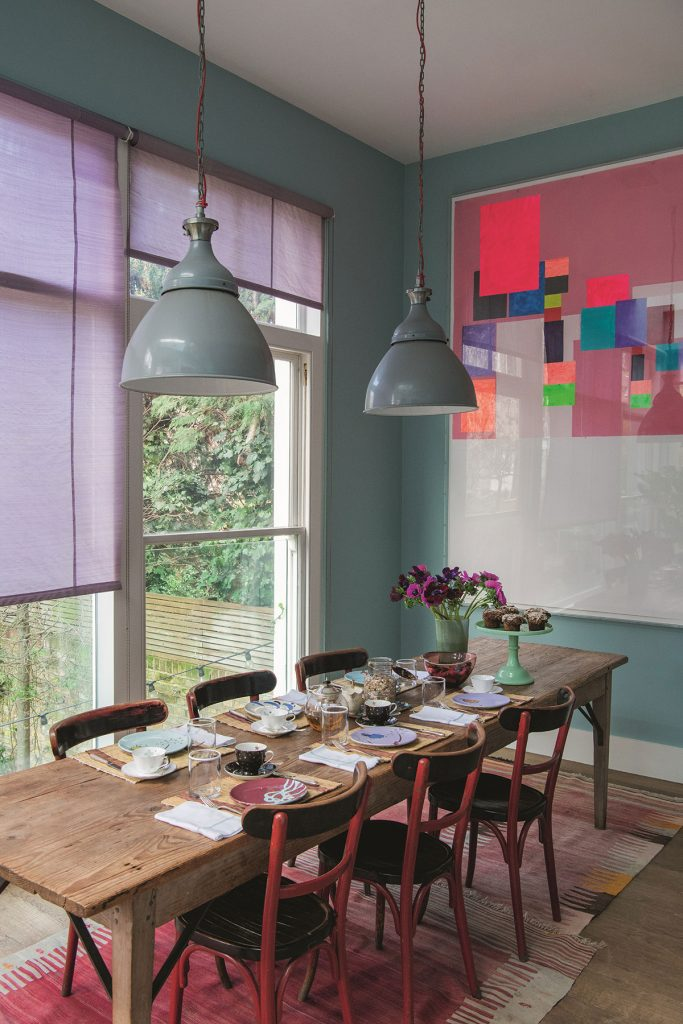 Home of Christine d'Ornano. Brightly coloured dining room, blue walls, purple blinds, modern art, vintage lightshades. © Ambroise Tézenas from Be My Guest: At Home with the Tastemakers, Flammarion, 2020. P241 Home of Patrick Perrin In this