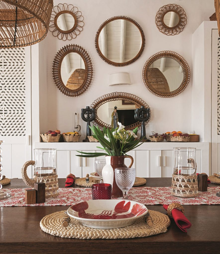 Home of Patrick Perrin. Table setting, cane lightshade, cane framed mirrors, lobster patterned plate © Ambroise Tézenas from Be My Guest: At Home with the Tastemakers, Flammarion, 2020