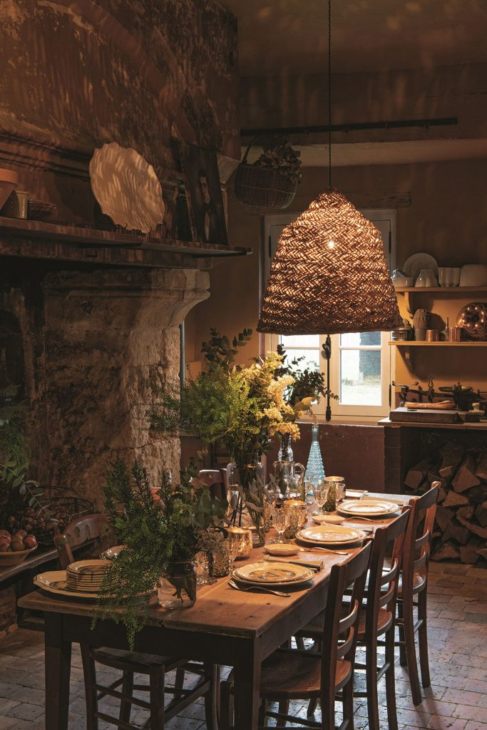 Home of Jean-Baptiste Martin and Vincent Farelly. Rattan lightshade, rustic dining room, stone fireplace, fresh foliage. © Ambroise Tézenas from Be My Guest: At Home with the Tastemakers, Flammarion, 2020