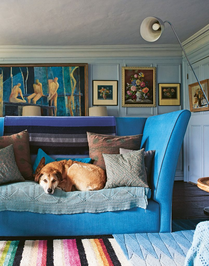 Nikki Tibbles' panelled blue living room with blue sofa, eclectic art and dog Ronnie. From Cool Dogs, Cool Homes by Geraldine James. Photo: James Gardiner
