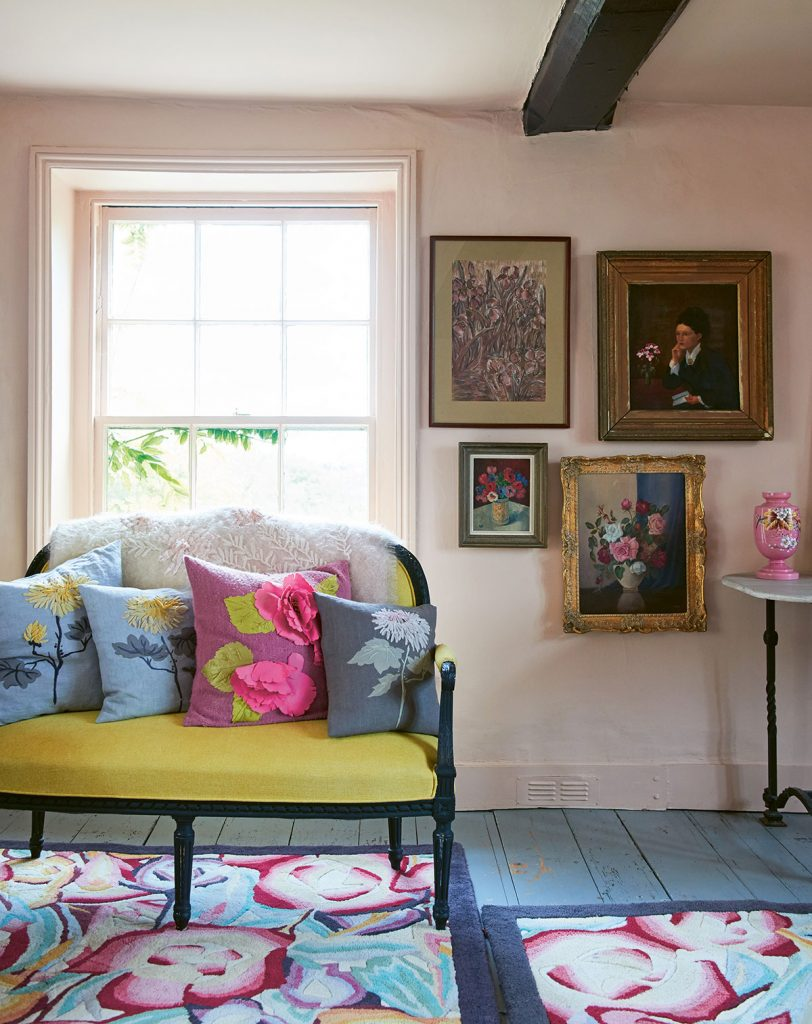 Nikki Tibbles yellow sofa with floral cushions, pink walls, blue painted floorboards. From Cool Dogs, Cool Homes by Geraldine James. Photo: James Gardiner