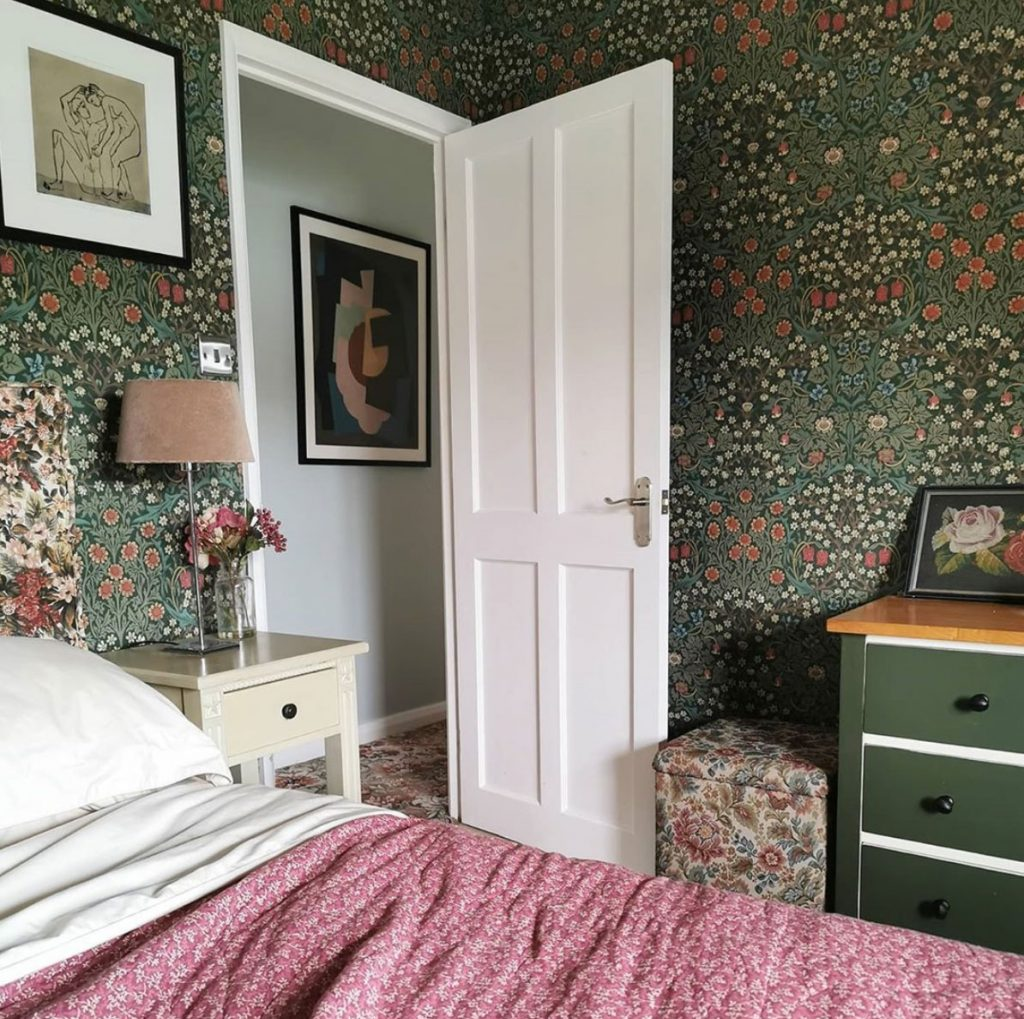 Laura Hunter bedroom with Morris & Co Blackthorn wallpaper, view through door with modern art and pink bedspread