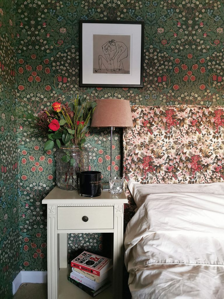 Laura Hunter bedroom, bedside detail with Morris & Co Blackthorn wallpaper, white bedside table, framed line drawing and floral headboard