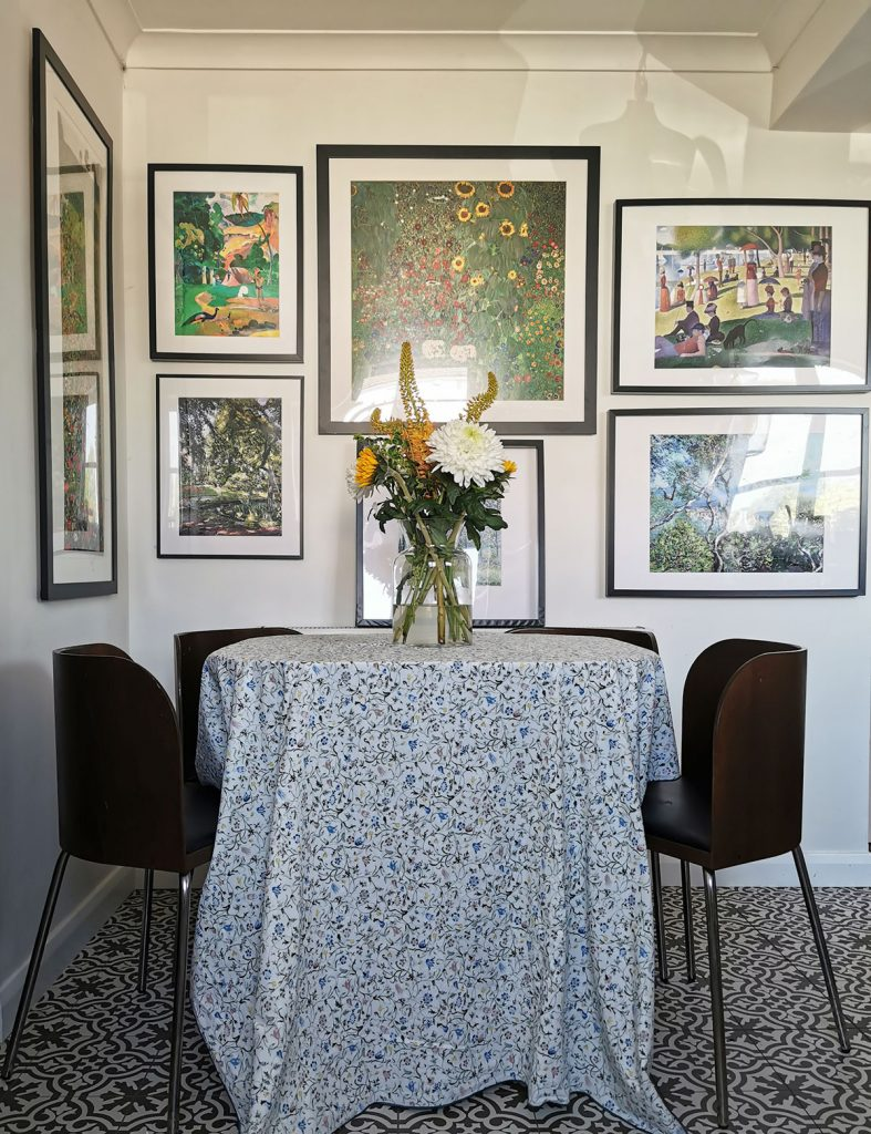 Laura Hunter dining table with floral tablecloth and framed artwork