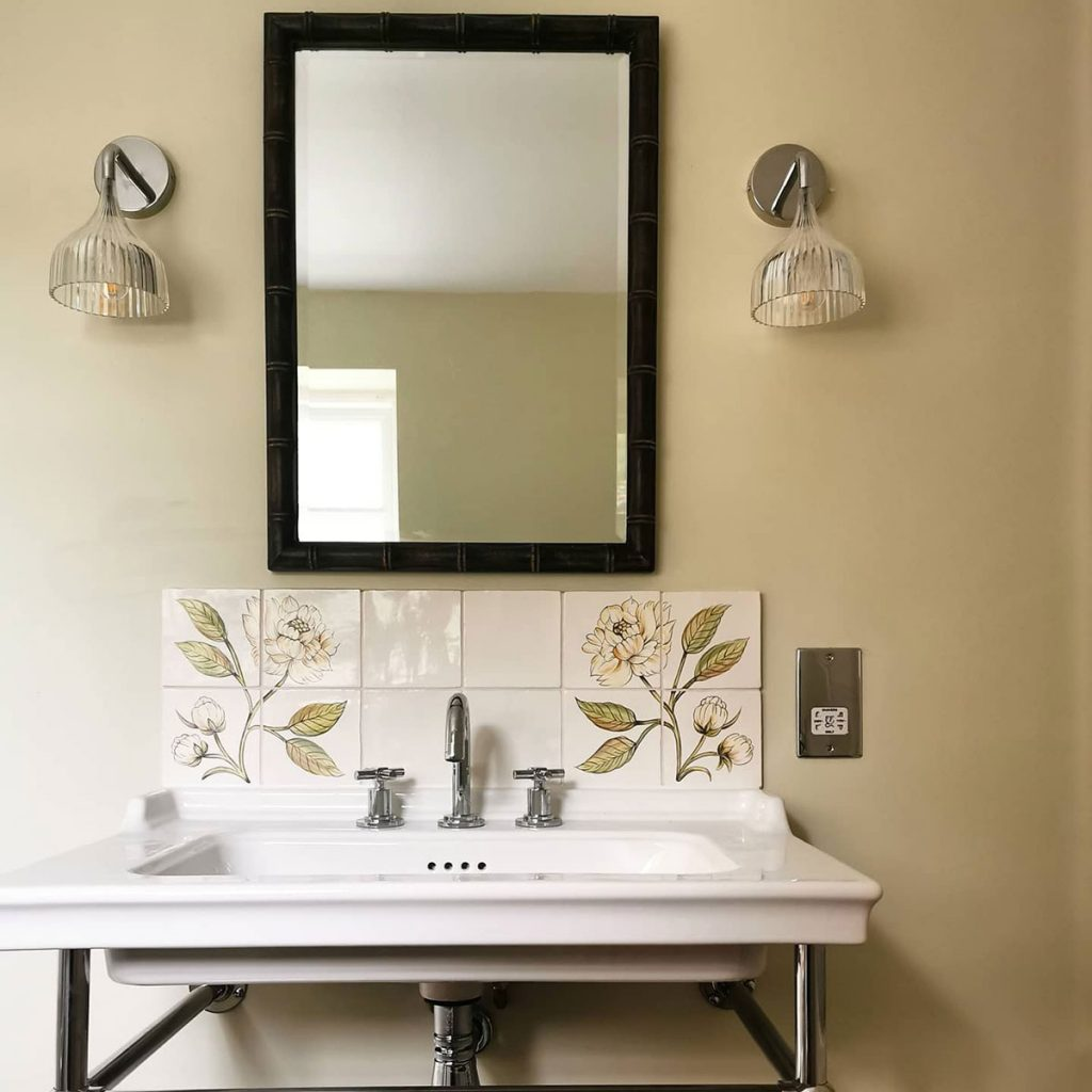 Laura Hunter bathroom sink with floral tiles and wall lights