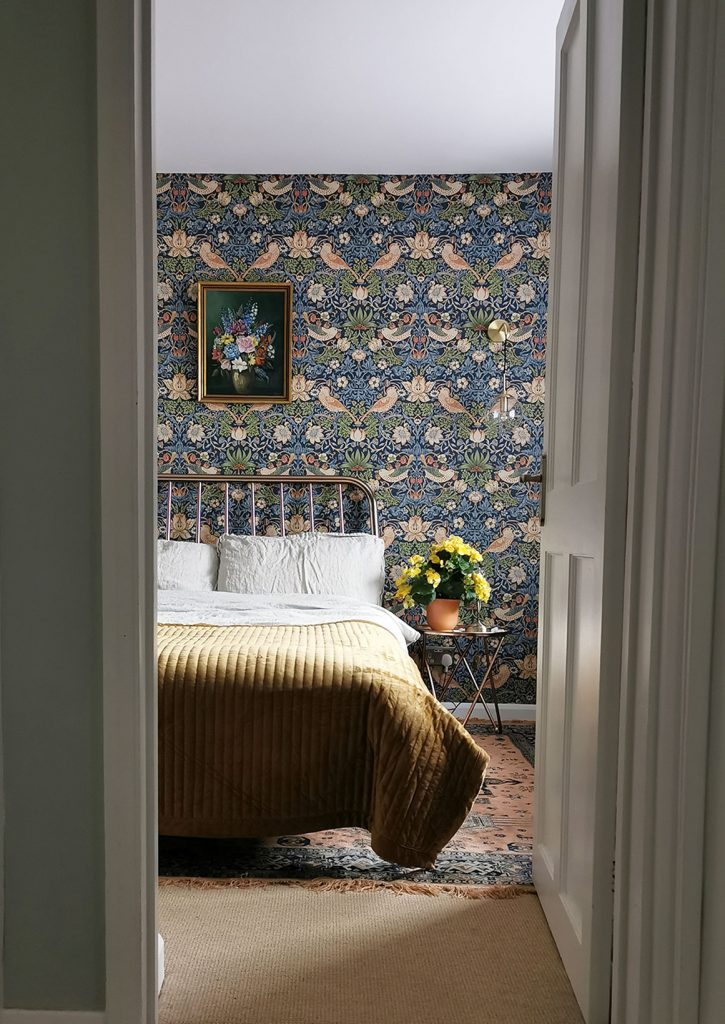 Laura Hunter bedroom with Morris & Co Strawberry Thief wallpaper, ochre bedspread, floral painting and yellow flowers