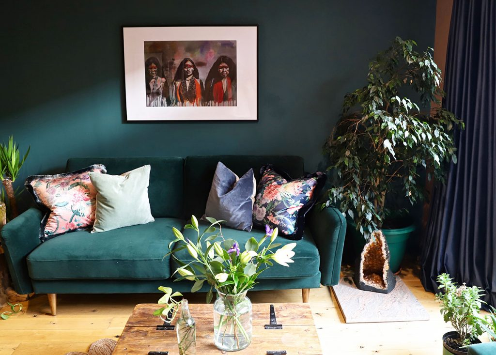 Design Havens for Heroes recipient Dr Claire's living room makeover with dark teal walls, deep green velvet sofa, floral cushions and botanicals