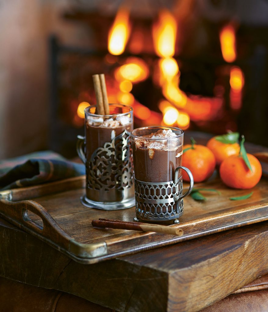 Cinnamon and Clementine Hot Chocolate on wooden tray with cinnamon sticks in front of roaring fire. From Winter Drinks published by Ryland Peters & Small