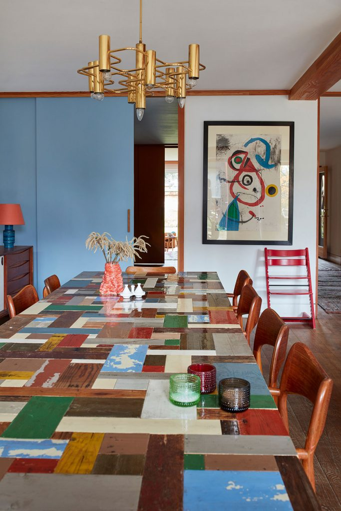 Colourful dining room with modern art, light blue wall and patchwork dining table from Everything by Abigail Ahern