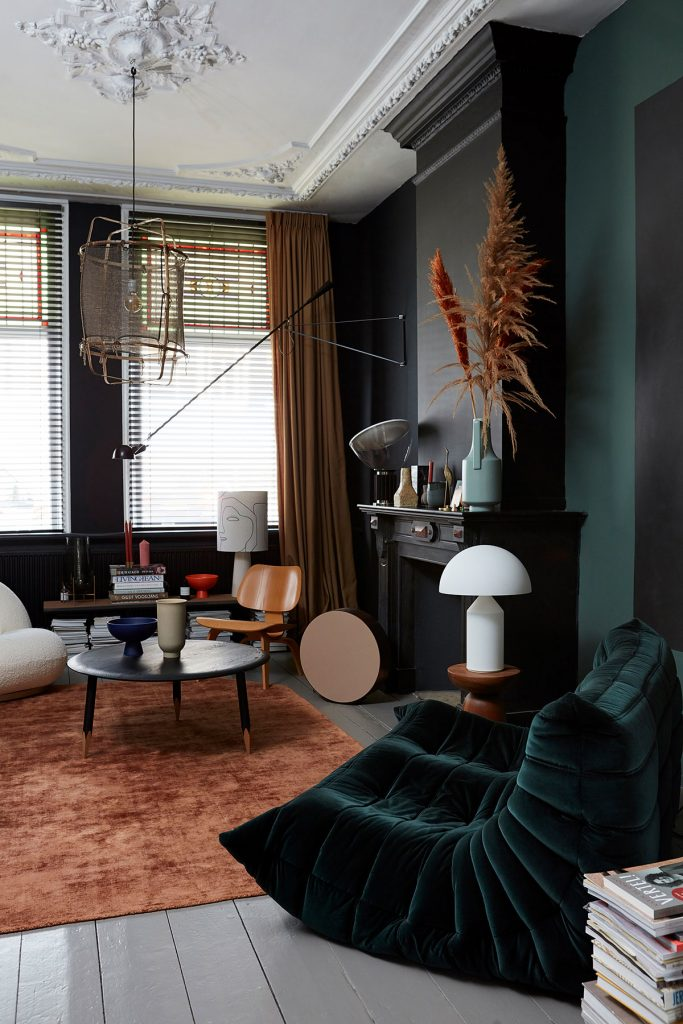 Dark green living room with black fireplace, russet rug and Ligne Roset Togo armchair from Everything by Abigail Ahern