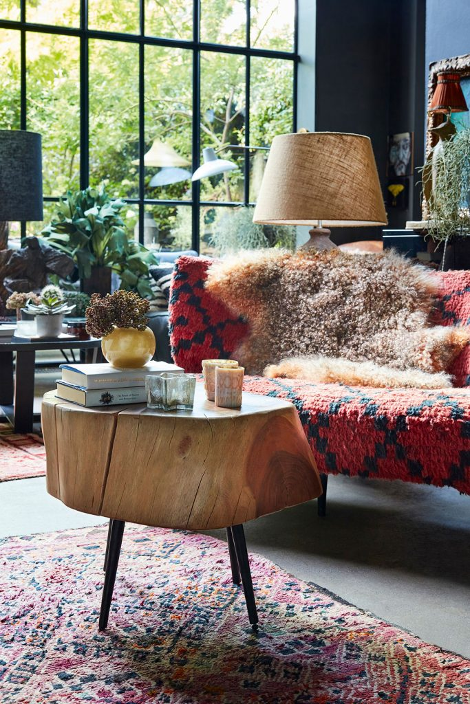 Abigail Ahern's living room with red sofa, rustic wooden coffee table and oversized lamp from Everything: A Maximalist Style Guide by Abigail Ahern book jacket