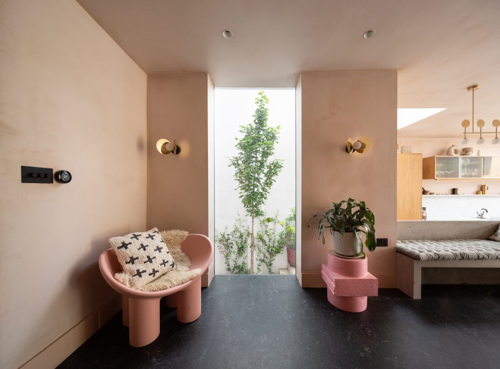 Gemma Ruse kitchen seating area with raw plaster walls, pink seating, brass disc lighting. Photography by Fraher & Findlay/AdamScott
