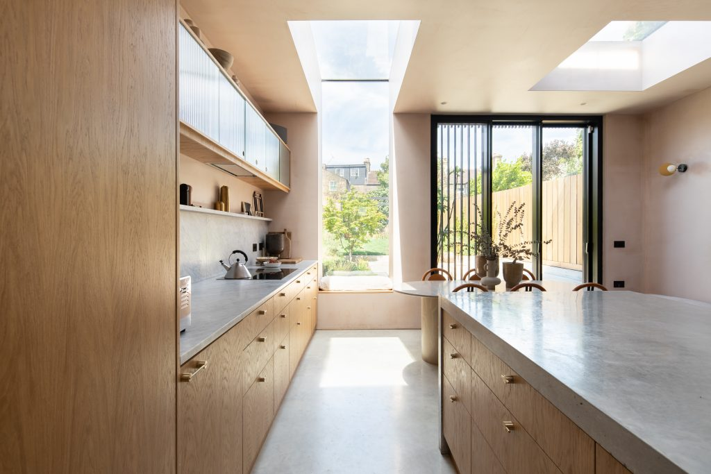 Gemma Ruse kitchen view to garden, with oak veneer units and marble worktops. Photography by Fraher & Findlay/AdamScott