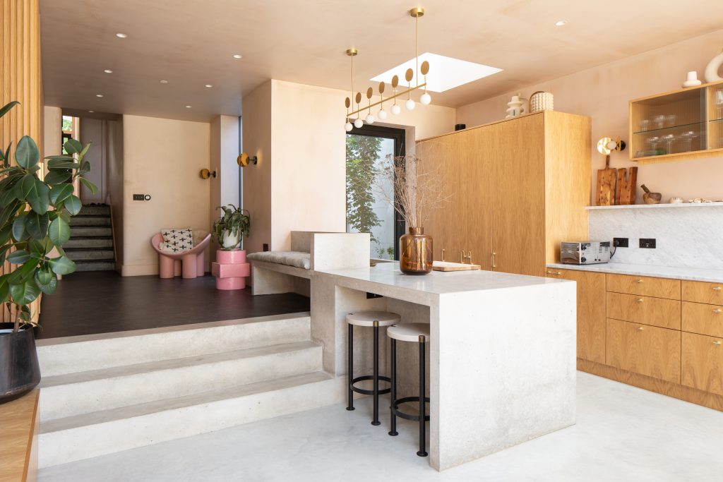Gemma Ruse kitchen with oak veneer units, polished concrete island and seating area. Photography by Fraher & Findlay/AdamScott