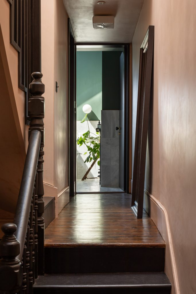 Gemma Ruse hallway with raw plaster walls and black painted staircase. Photography by Fraher & Findlay/AdamScott