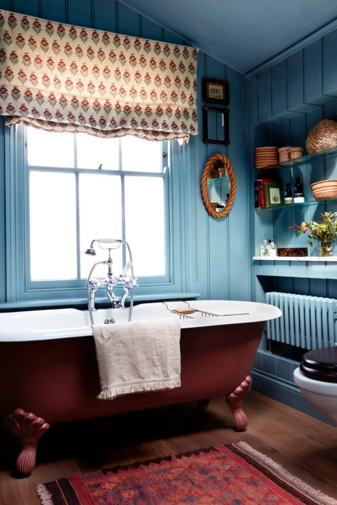 Interior Designer Lonika-Chande's-bathroom with deep red freestanding bath, blue shiplap walls and patterned fabric blind