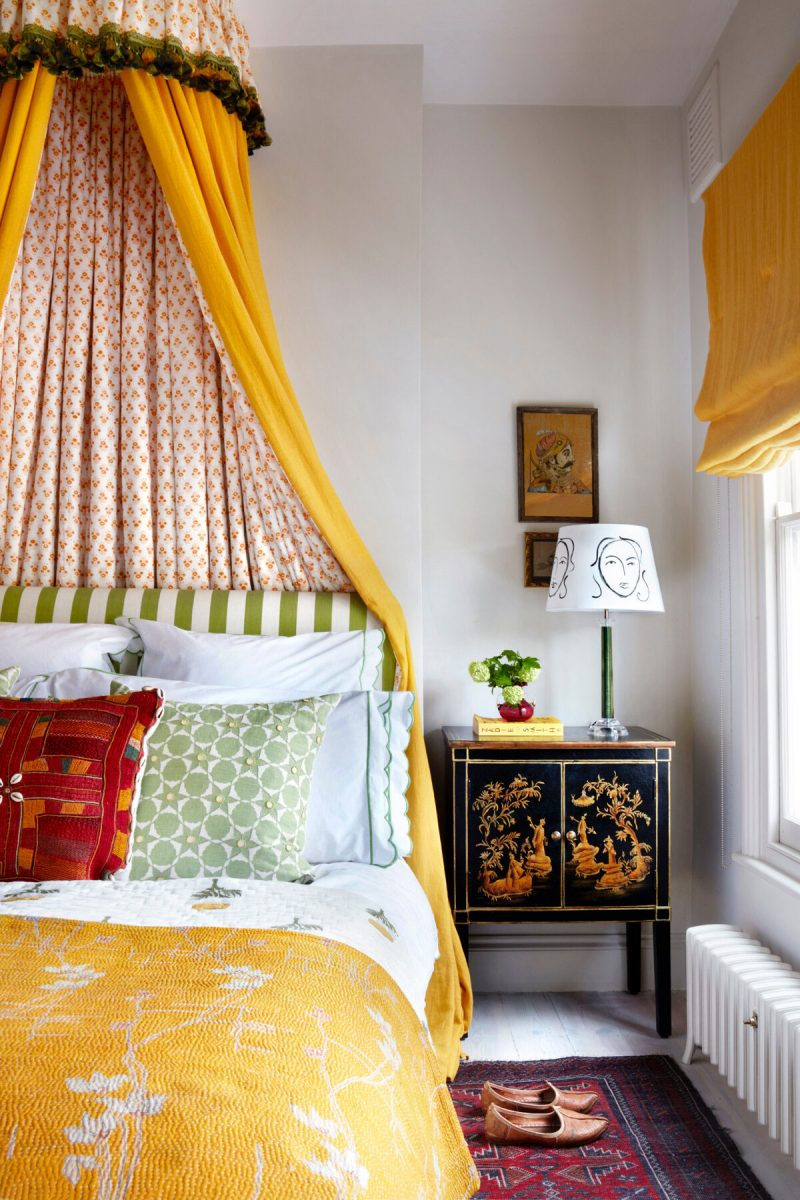 Interior Designer Lonika-Chande's-master-bedroom with yellow and red fabric bed canopy, chinese bedside table, yellow bedspread and green stripe headboard