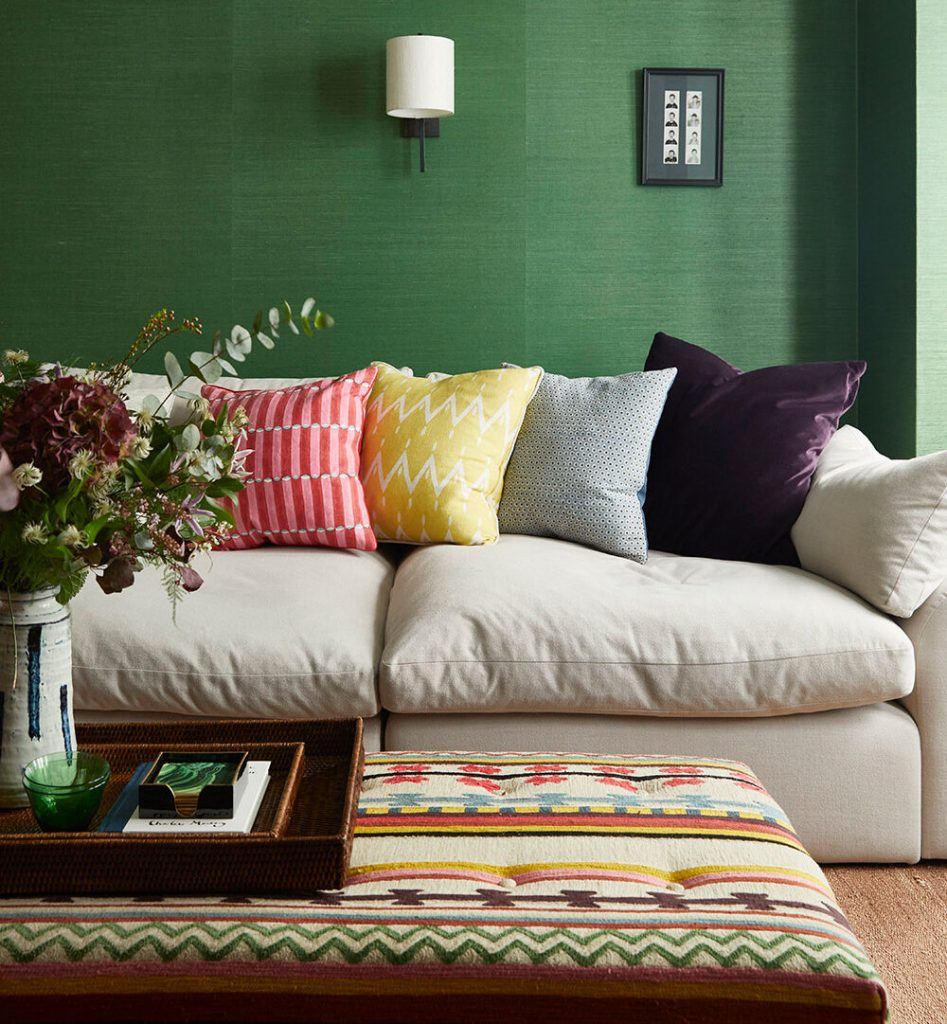 Living room with emerald green papered walls and colourful textiles designed by Sophie Pringle of Pringle and Pringle interior design studio