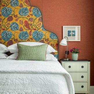 Kit-Kemp-yellow botanical headboard-in-orange-bedroom. Image: Simon Brown
