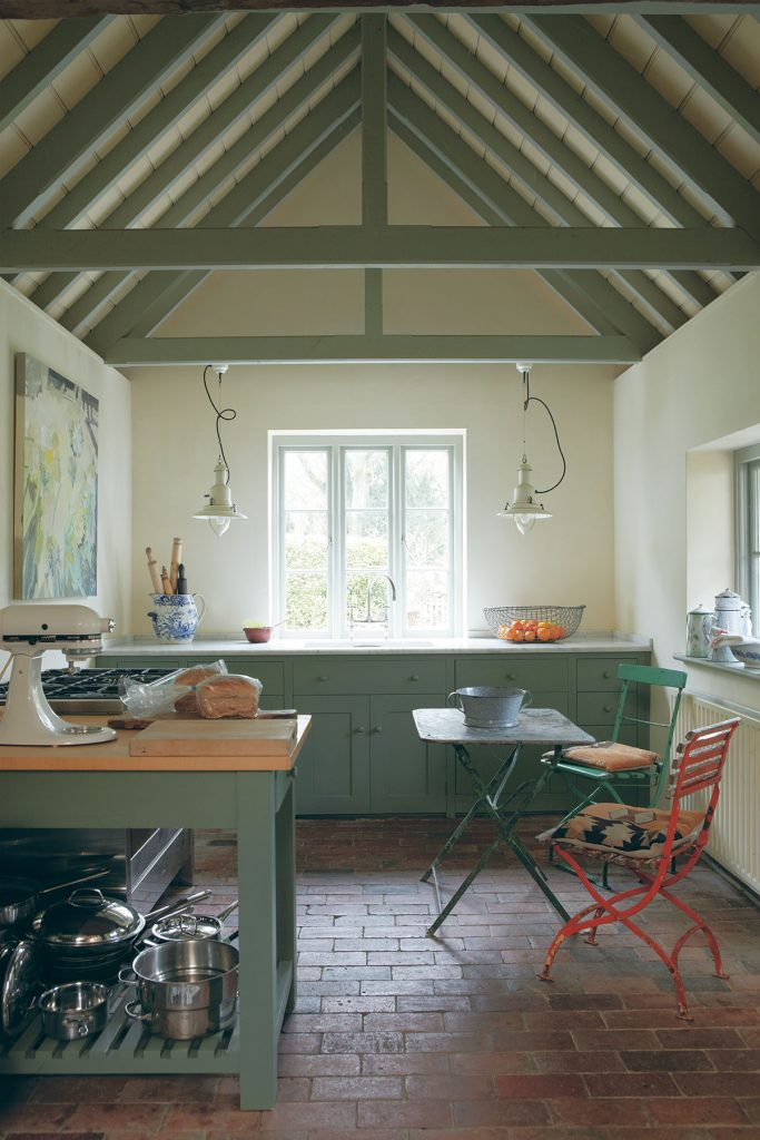 Sage green kitchen and tiled floor at the cottage of artist Sandra Whitmore, kitchen by Plain English. Image by Jan Baldwin