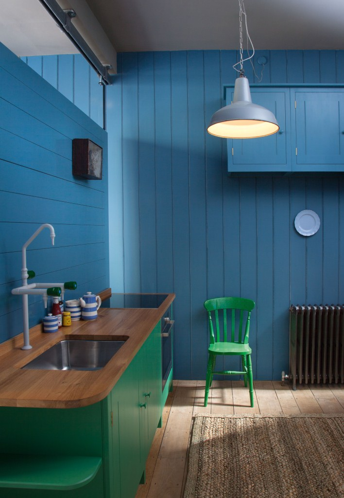 Blue tongue and groove walls and green kitchen by British Standard
