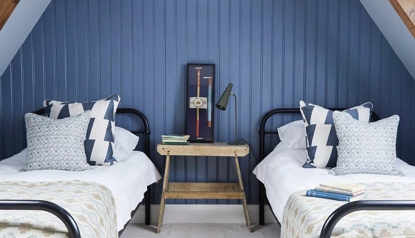 blue tongue and groove wall in pitched bedroom by Lauren Caisley Interiors